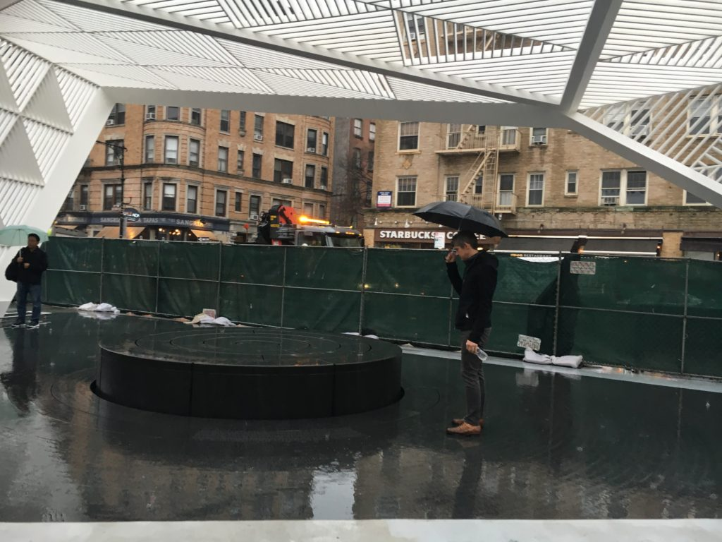 "Paul Kelterborn, cofounder of New York AIDS Memorial, stands near the fountain, looking down at the apex where the etched words from Walt Whitman's ""Song of Myself"" poem begins. The picture was taken on a raining afternoon the day before the unveiling of the site. Photo by Kemi Osukoya"